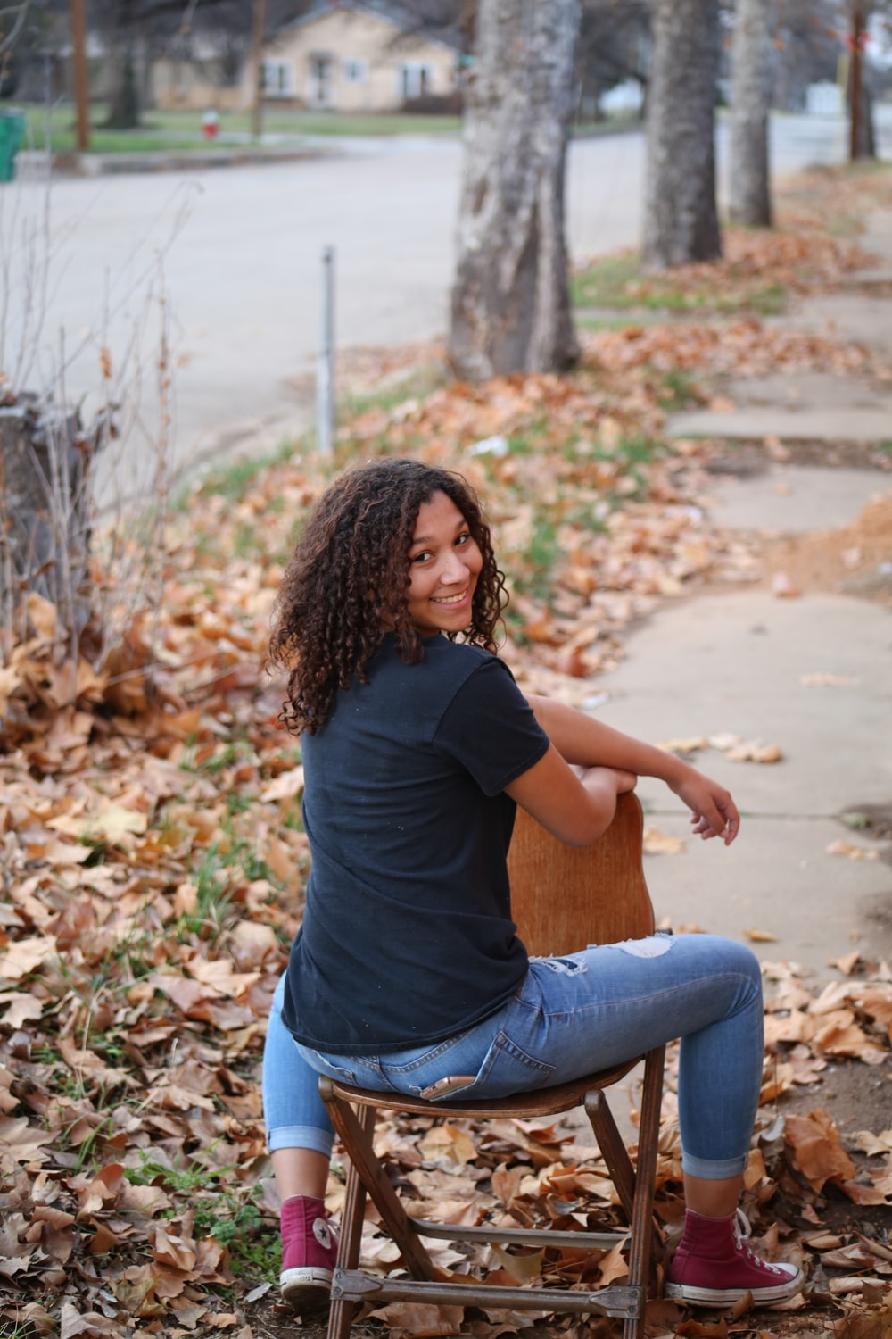 woman in black t-shirt and blue denim jeans sitting on brown dried leaves during daytime