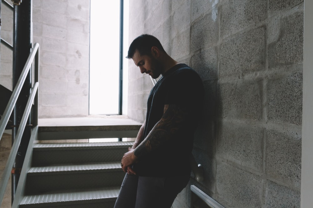 man in black t-shirt and brown pants standing on staircase