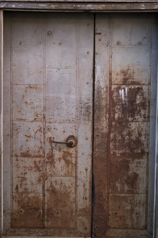 grey wooden door with brass door knob