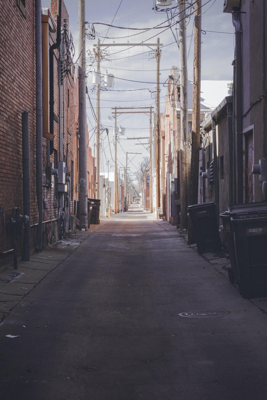 empty street between brown brick buildings during daytime