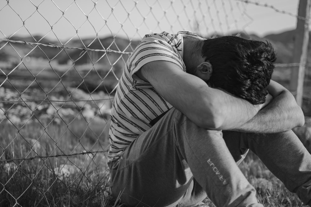 man in black and white stripe t-shirt leaning on chain link fence
