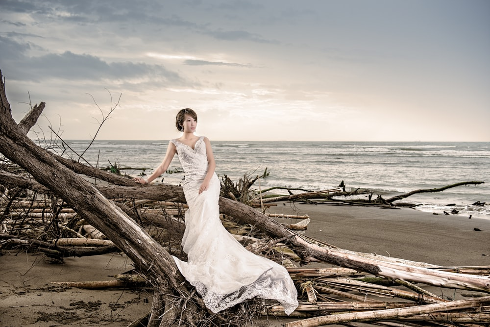 woman in white wedding dress standing on brown wood log near body of water during daytime