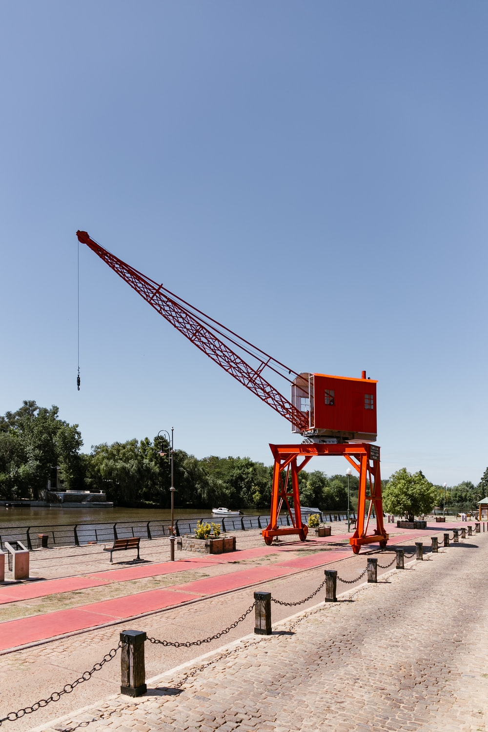 red crane on brown concrete floor during daytime