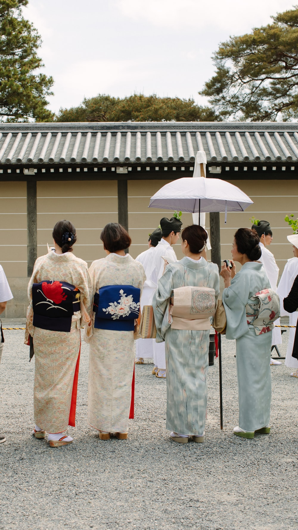 group of people wearing white and yellow floral kimono standing on gray concrete floor during daytime