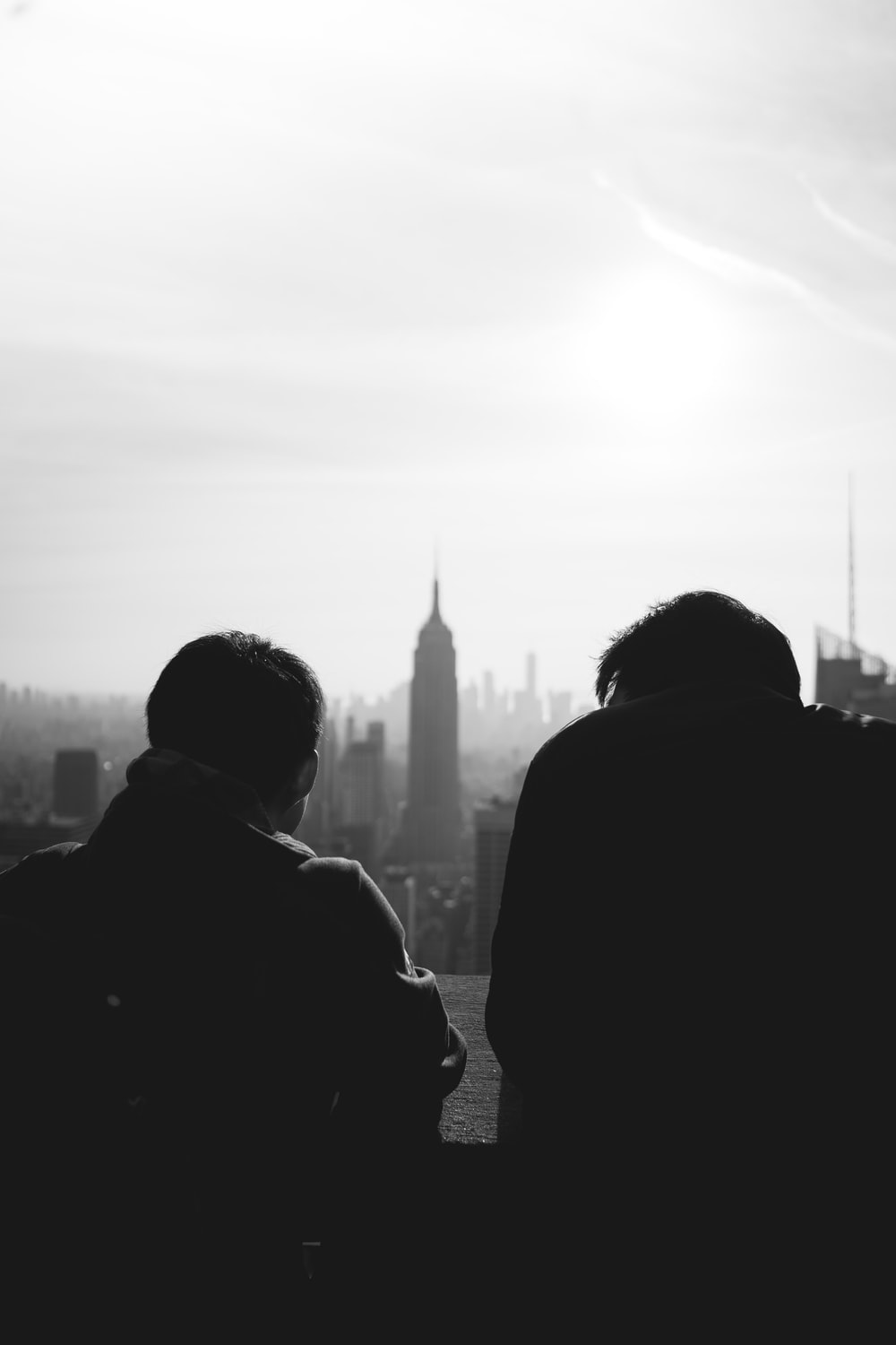 silhouette of 2 person standing near high rise building during daytime