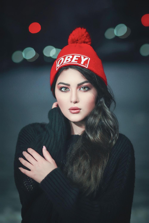 woman in black sweater wearing red cap