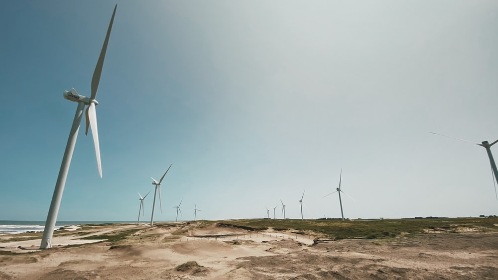 wind turbines on brown sand under blue sky during daytime