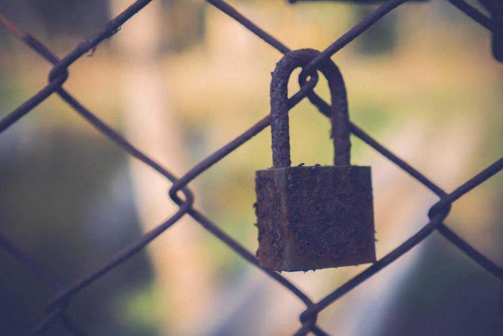 brown padlock on gray metal fence