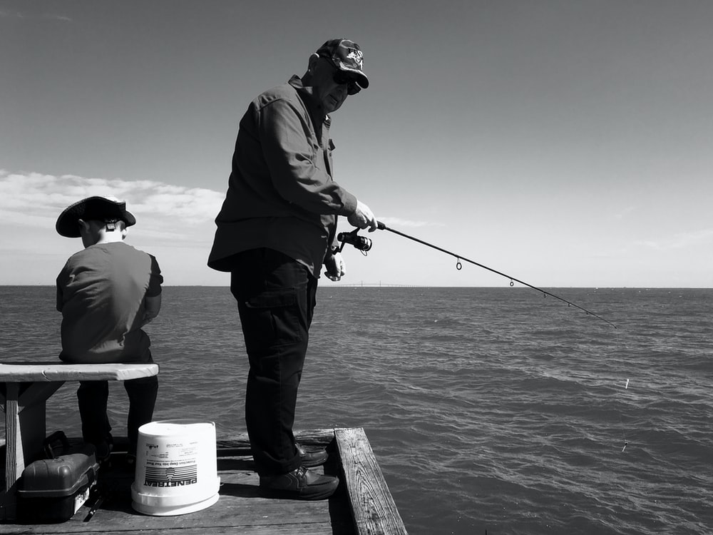 man in black jacket and pants fishing on sea