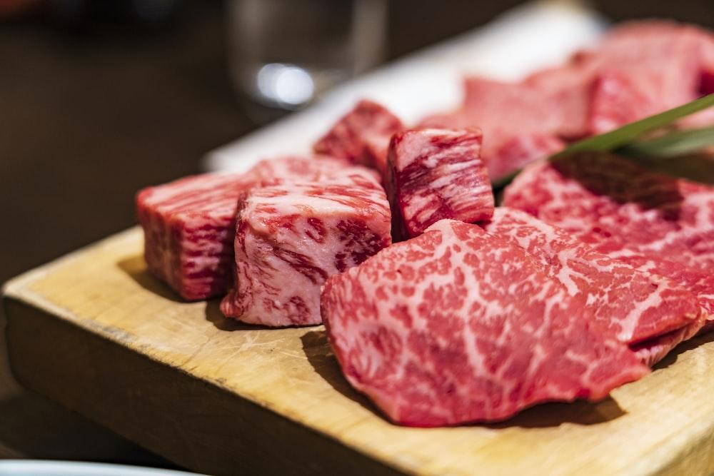 茶色の木製のまな板に生の肉をスライス
