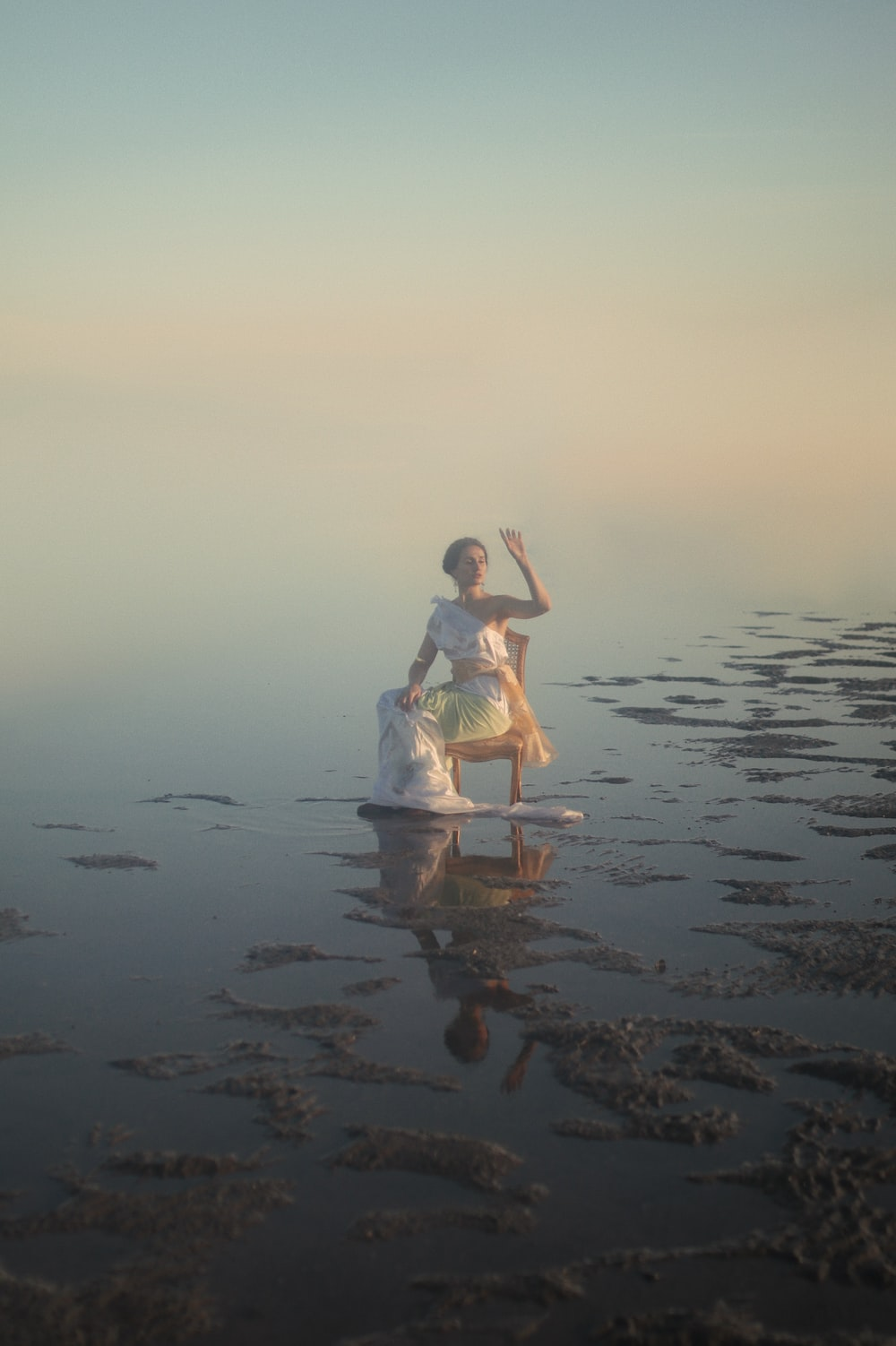 woman in white dress sitting on brown wooden chair on beach during sunset