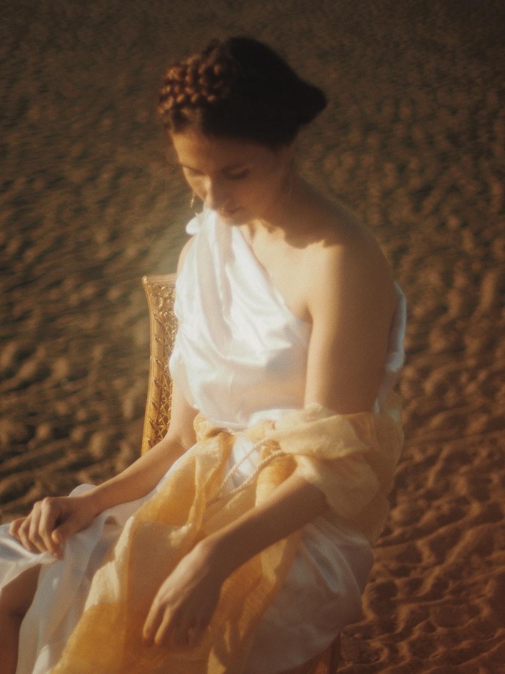 woman in white sleeveless dress sitting on brown textile