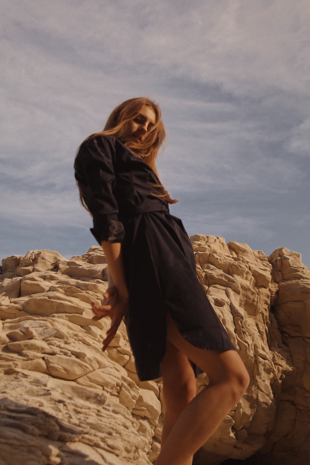 woman in black dress standing on brown rock formation during daytime