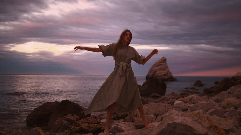 woman in brown dress standing on rock near sea during daytime