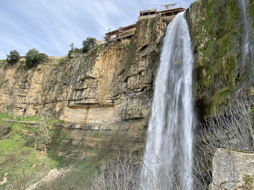 waterfalls on rocky mountain under blue sky during daytime
