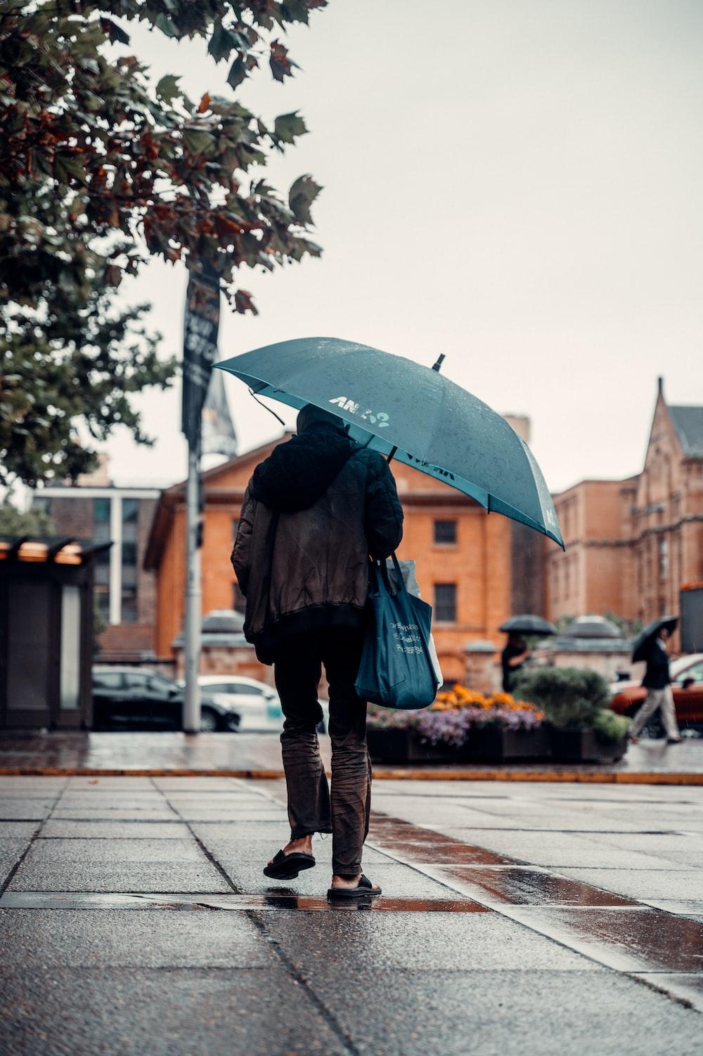 woman in black jacket and blue denim jeans holding umbrella walking on sidewalk during daytime