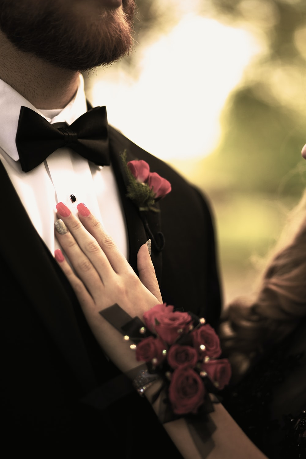 man in black suit jacket holding red rose bouquet