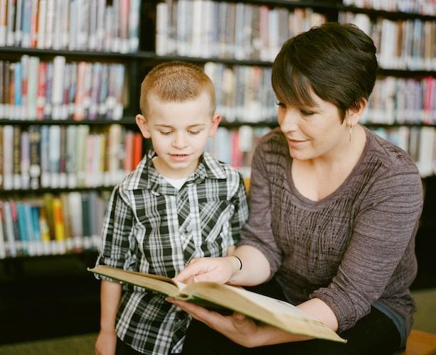 Une mère apprend à son fils à lire. | Photo : Unsplash