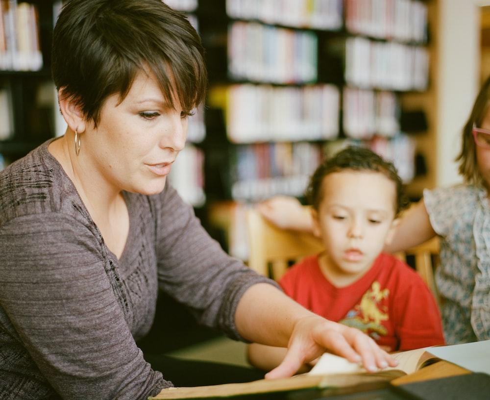 woman in gray long sleeve shirt sitting beside boy in orange crew neck shirt