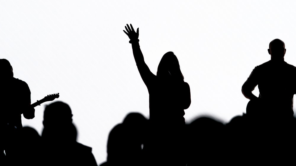 silhouette of people raising their hands