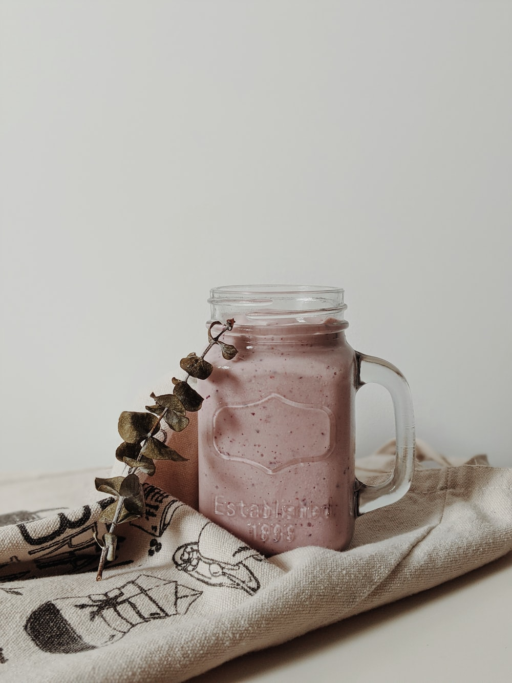 clear glass jar with pink liquid inside