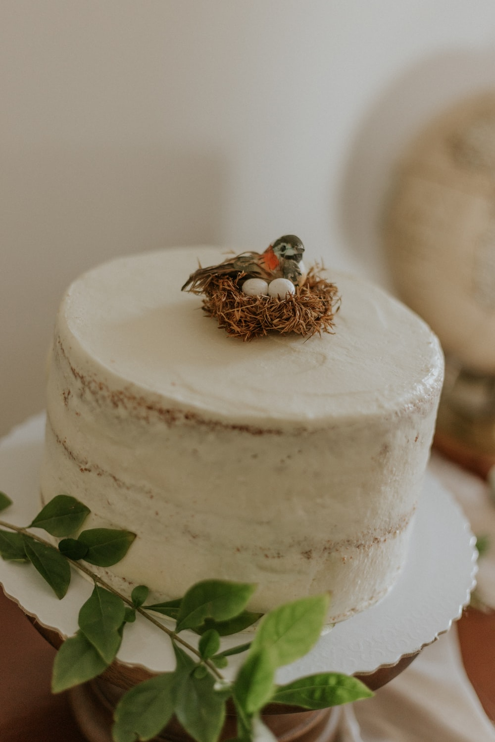 white round cake with green leaves on top