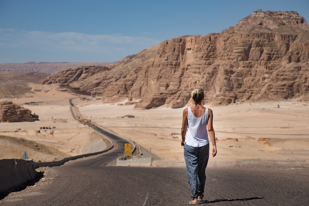 woman in white tank top and blue and white plaid pants standing on gray asphalt road