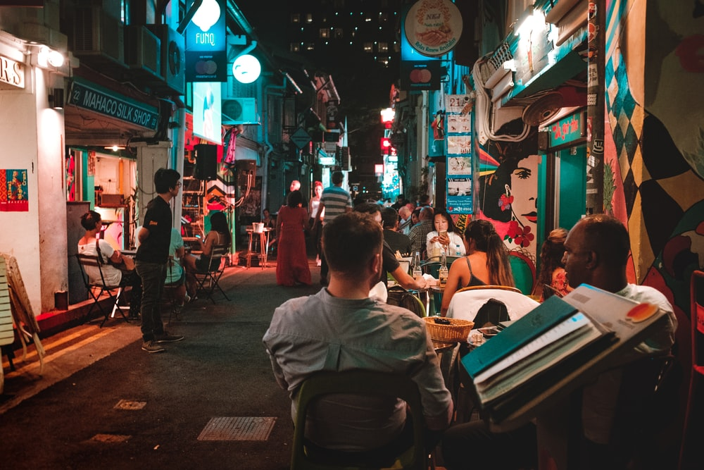 people sitting on chair near street during night time