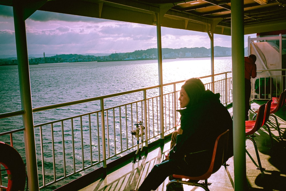 woman in black jacket sitting on chair near body of water during daytime