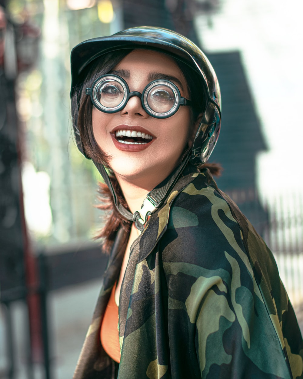 woman in green and brown camouflage jacket wearing black goggles