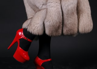 woman in white fur coat and red leather boots