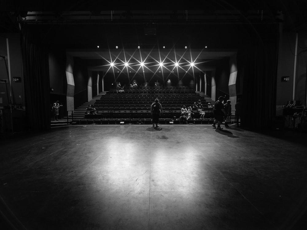 grayscale photo of people walking on hall