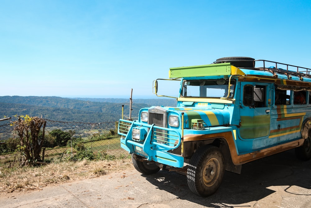 teal and brown truck on brown dirt road during daytime