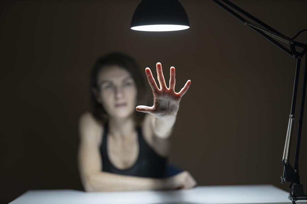 woman in black tank top raising her hands