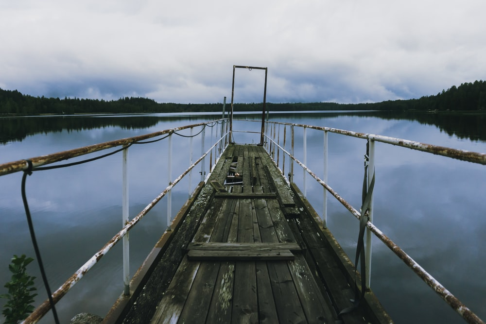 brown wooden dock over body of water under cloudy sky during daytime