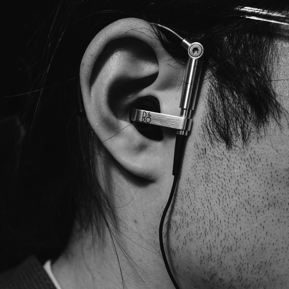 grayscale photo of woman with black earbuds