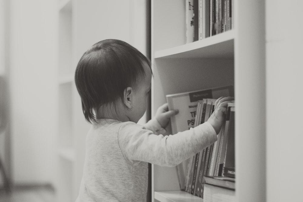 child in white long sleeve shirt standing beside white wooden shelf