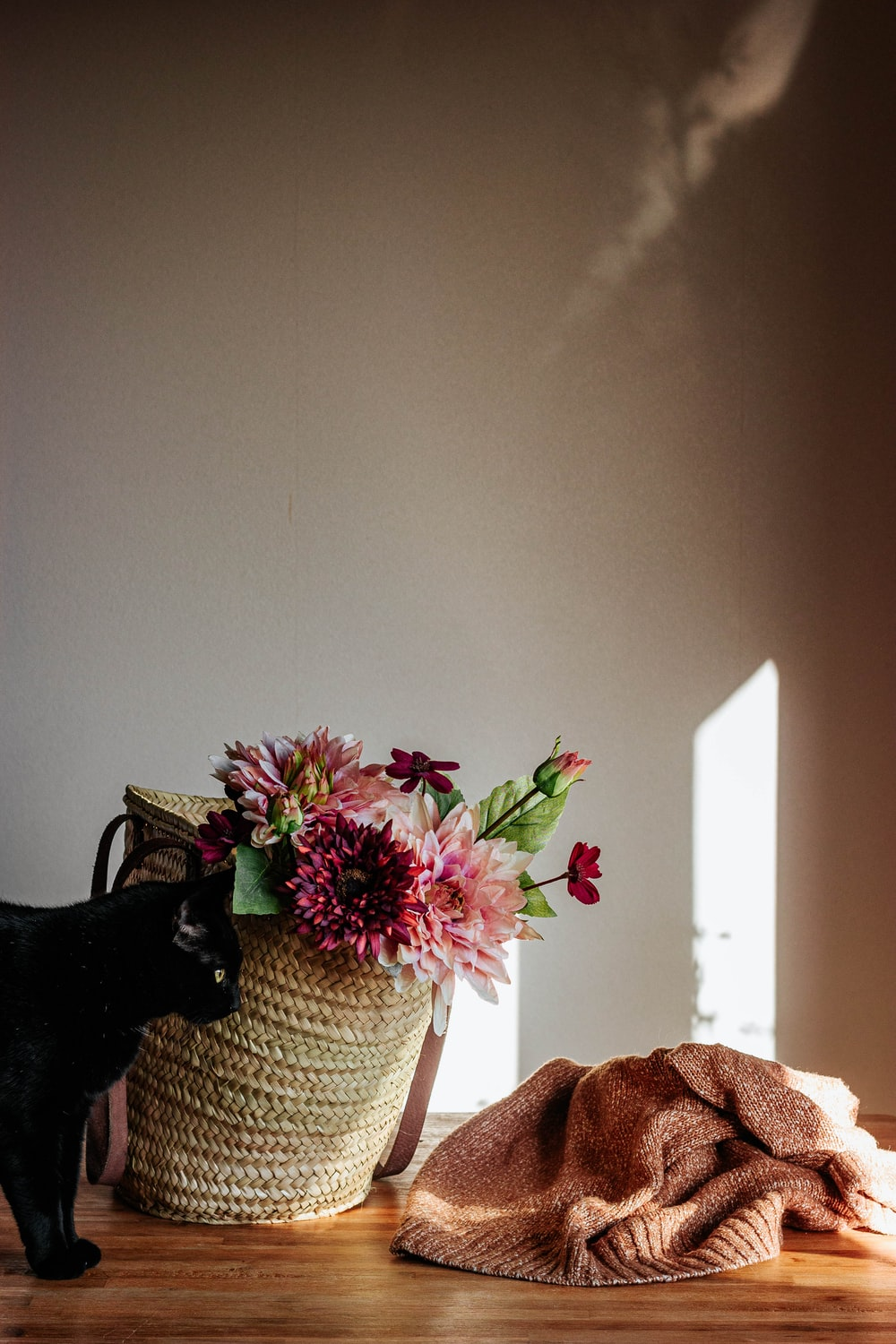 pink and yellow flower on white wicker basket
