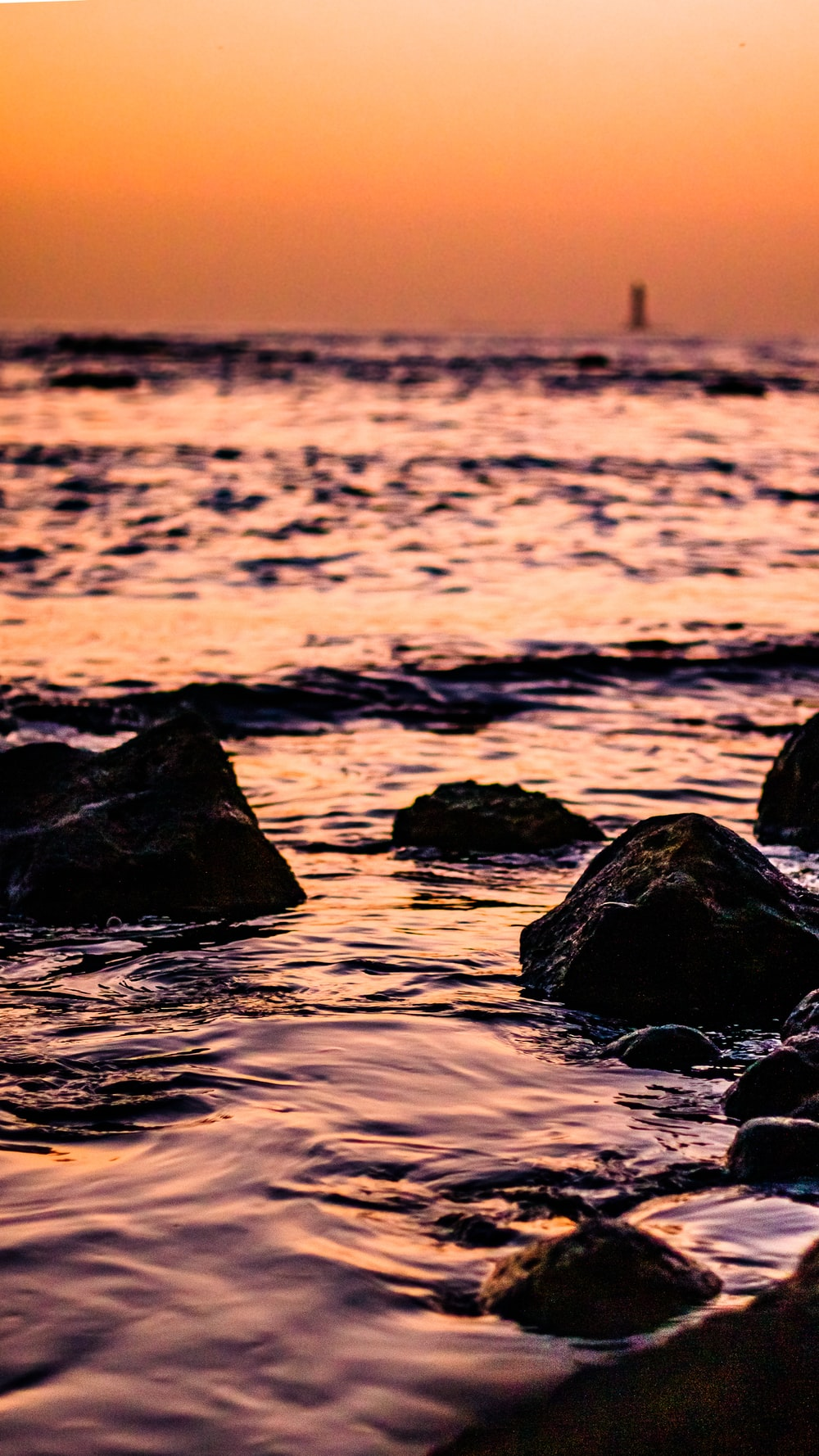black rocks on body of water during sunset