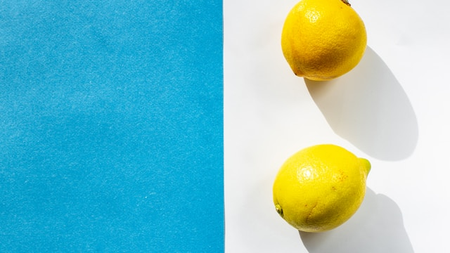 yellow lemon fruit on blue surface