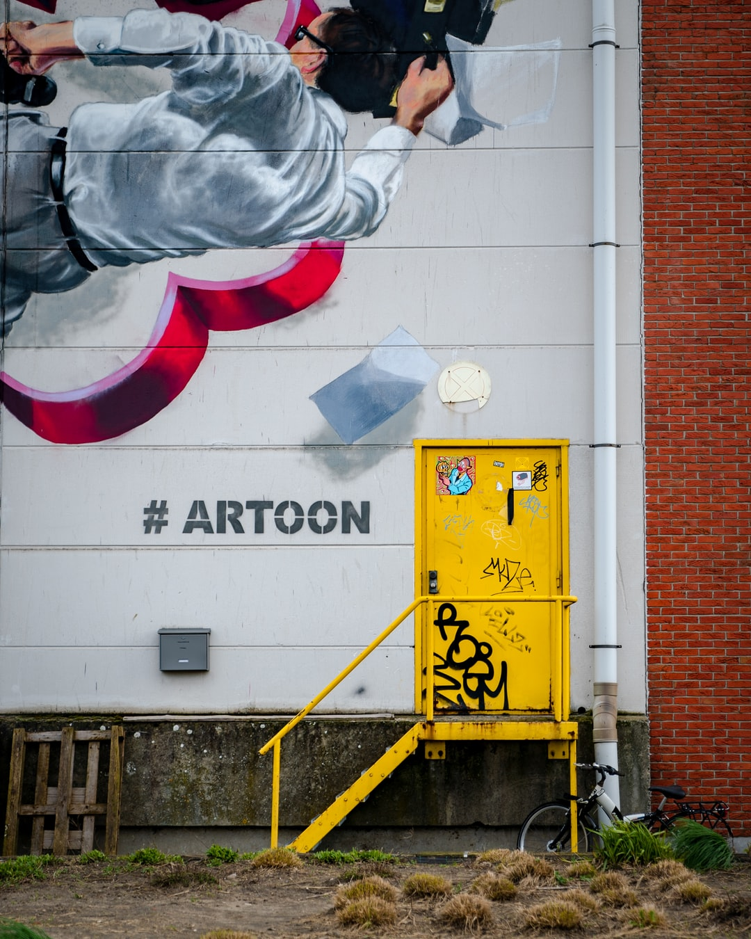 Grafitti in Antwerpen. This is a warehouse at the harbour with a stylish yellow door and #artoon.