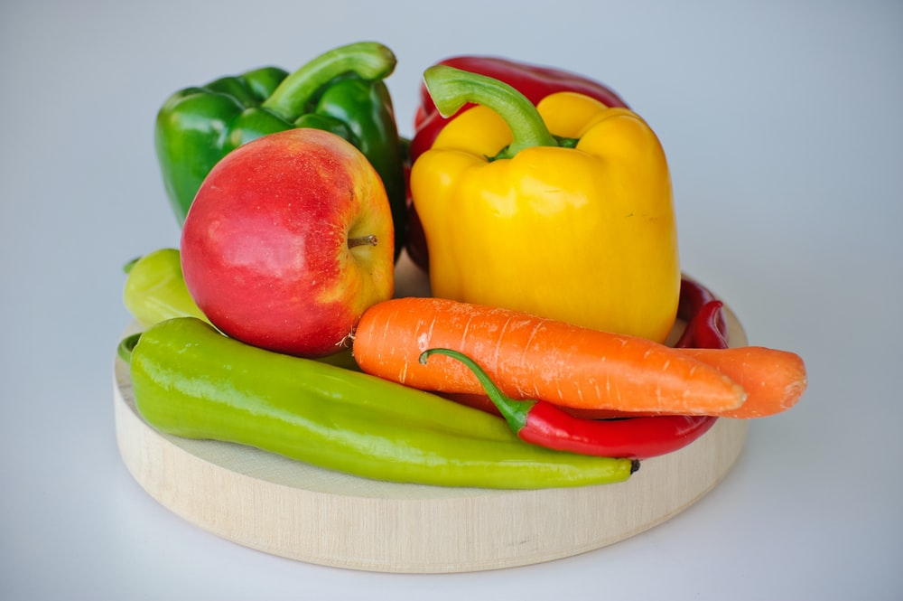 red and green bell pepper and red apple on white plate