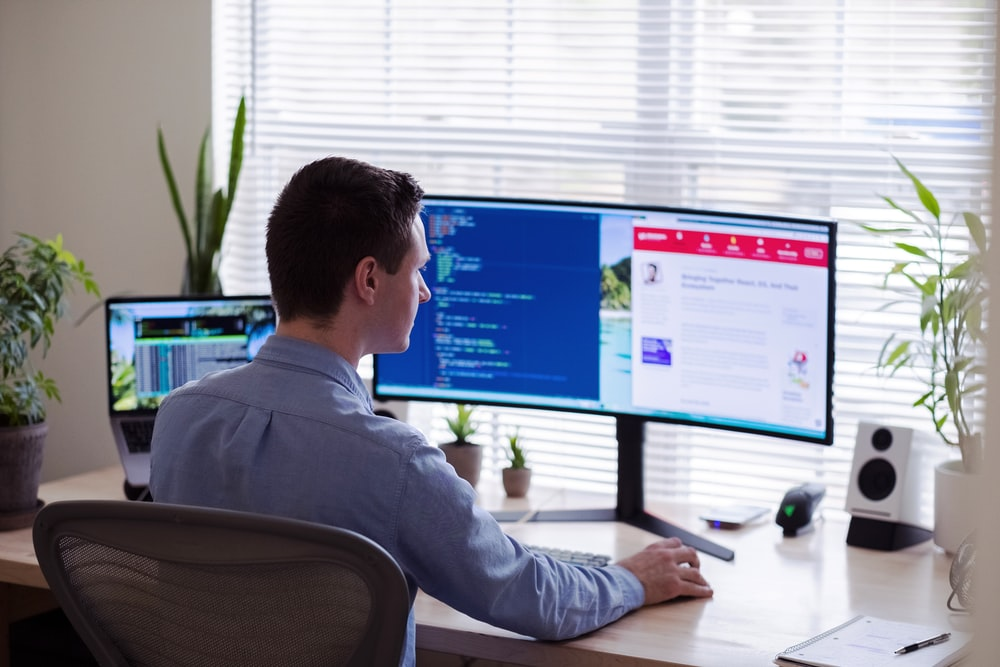 man in gray dress shirt sitting on chair in front of computer monitor