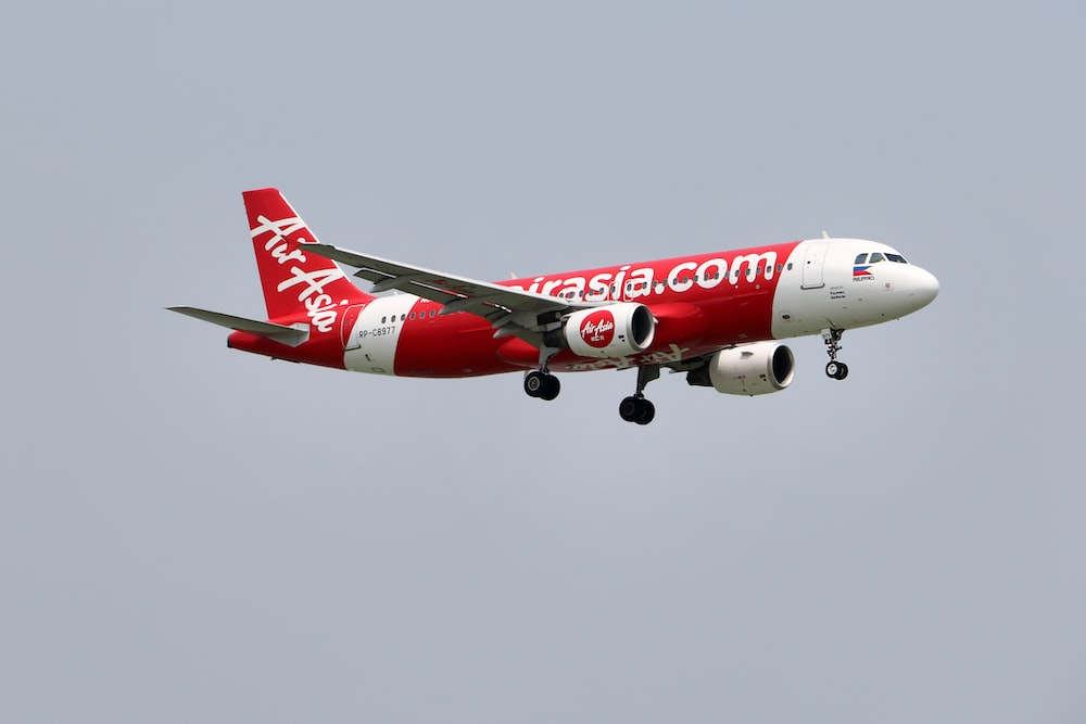 red and white passenger plane in flight
