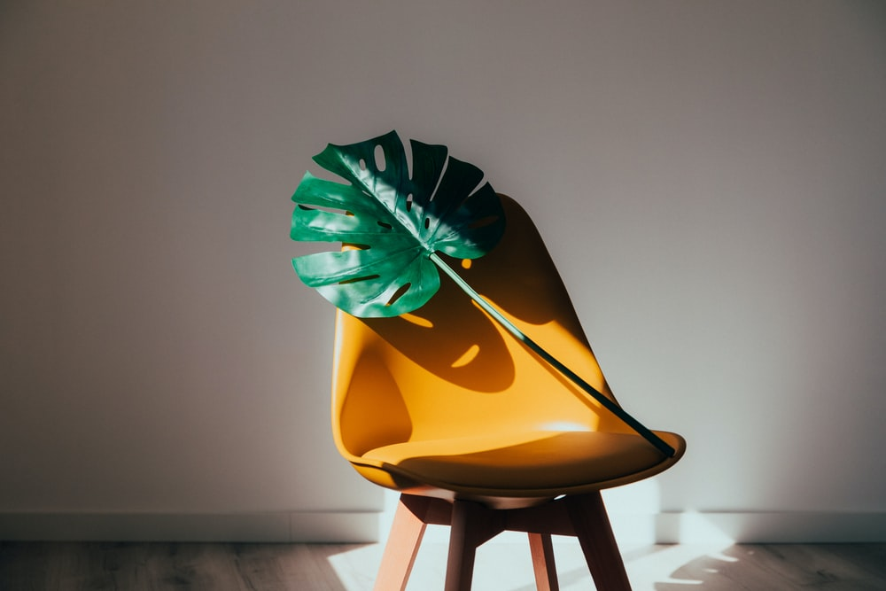 yellow and green umbrella on brown wooden stool