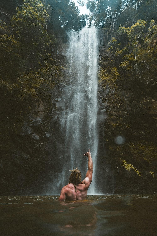 person sitting on rock near waterfalls during daytime