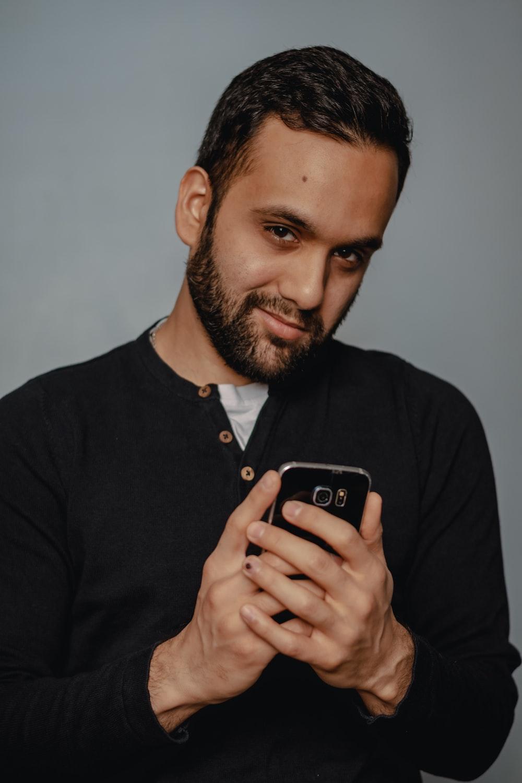 man in black henley shirt holding black smartphone