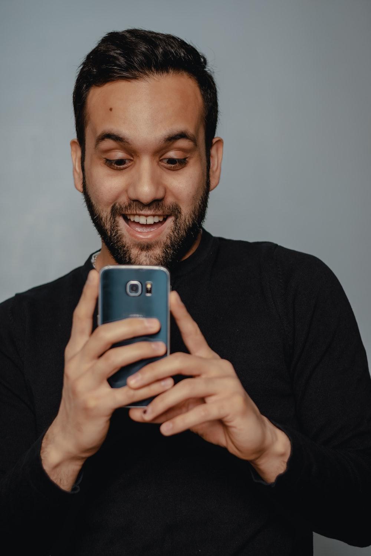 青いスマートフォンを保持している黒のクルーネック長袖シャツの男