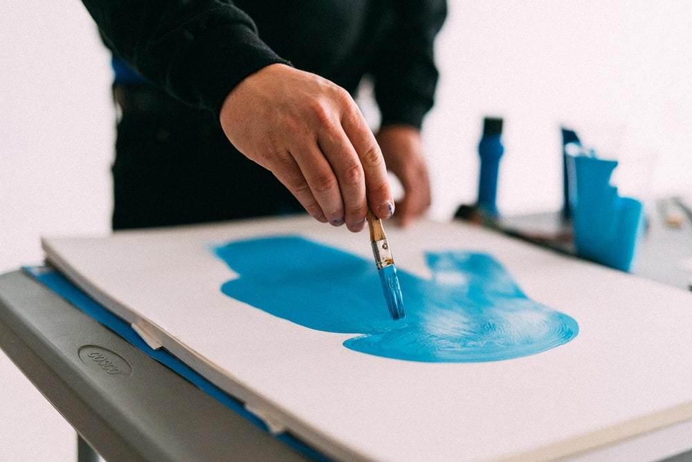person holding blue paint brush
