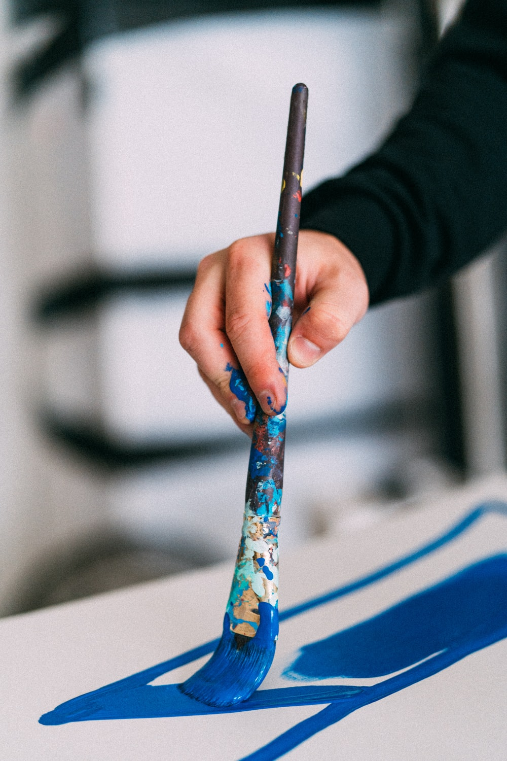 person holding blue and white paint brush